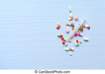 syringe and pills on white background, top view