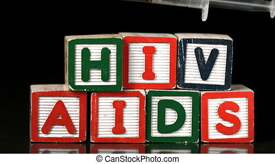 Syringe falling on blocks spelling Aids and Hiv in slow...