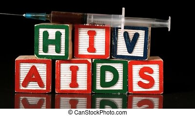Syringe falling on wooden blocks spelling Aids and Hiv in...