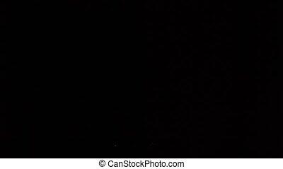 Syringe in a super slow motion falling on a black floor