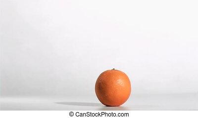 Syringe in super flow motion falling in an orange