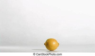 Syringe in super flow motion falling in a lemon against a...