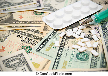 Syringe, tablet on money.