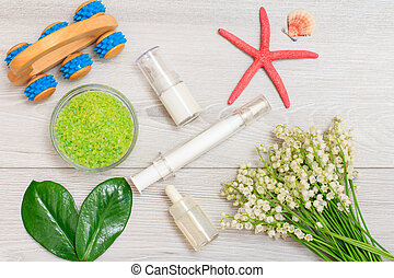 Syringe with eye cream, bottles with cream for face skin and aromatic oil, bowl with sea salt and bouquet of lilies of the valley.