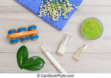 Syringe with eye cream, bottles with cream for face skin and aromatic oil, hand massager, bowl with sea salt and lilies of the valley on towel