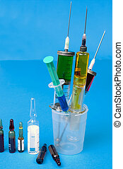 Syringes and ampoules on blue background