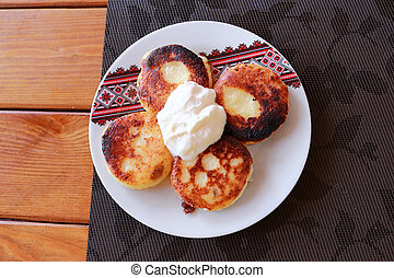 Syrniki - Cottage cheese pancakes, Fritters of cottage cheese - traditional Ukrainian and Russian cuisine.