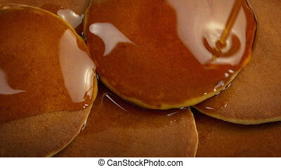 Syrup pouring on plate of pancakes