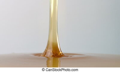 Closeup shot of thick syrup pouring on plain background