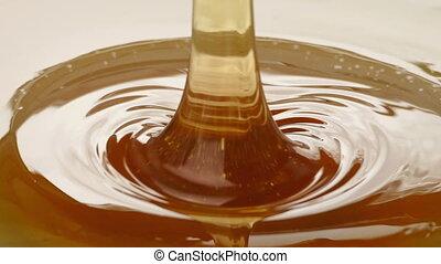 Syrup Pours Artistic Closeup - Honey pours onto plain white...