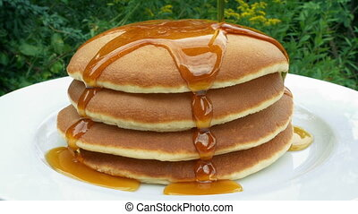 Syrup poured onto stack of breakfast pancakes in pretty garden area
