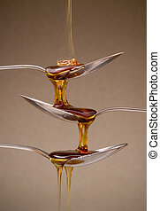 Warm brown syrup running down three spoons