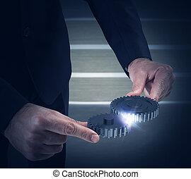 System of gears - Businessman engages two pieces of...