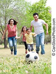 szülők, és, két, young gyermekek, játék futball, alatt, a, zöld terep, külső