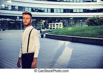 szőke, fiatalember, mellett, modern épület, alatt, város
