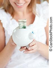 szőke, nő, takarékbetét pénz, alatt, egy, piggy-bank