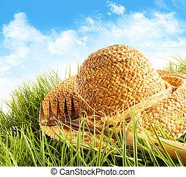 szalmaszál kalap, képben látható, fű