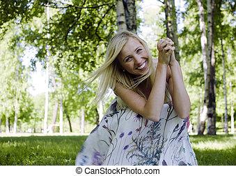 szczęśliwy, blond, młoda kobieta, w parku, uśmiechanie się