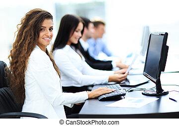 szczęśliwy, młody, kobieta interesu, przeglądnięcie za, i, jej, koledzy, pracujący, biuro