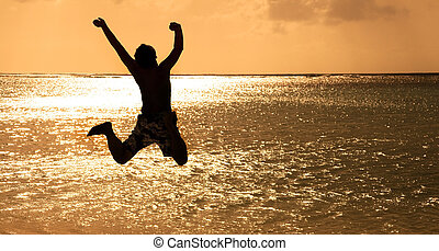 szczęśliwy, młody mężczyzna, skokowy, na plaży, na, zachód słońca