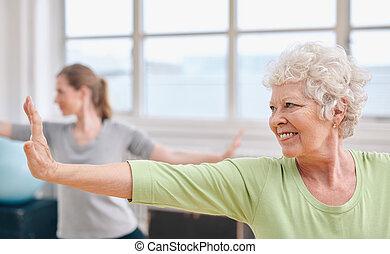 szczęśliwy, starsza kobieta, practicing, yoga, na, sala gimnastyczna, class.