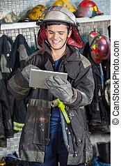 szczęśliwy, strażak, używając, palcowa pastylka