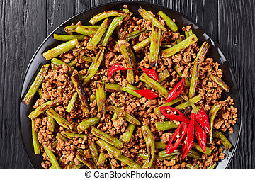 Szechuan Pork Stir Fry with charred Green Beans served on a...