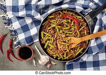 Szechuan Pork Stir Fry with Green Beans in a skillet on...