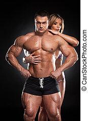 szexi, egészséges, szőke, leány, ölelgetés, from mögött, hím, bodybuilder., álló, együtt, felett, black háttér