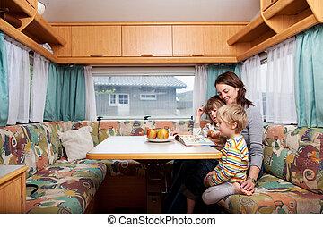 sztori, nő, fiak, vontatott lakókocsi, könyv, asztal,...