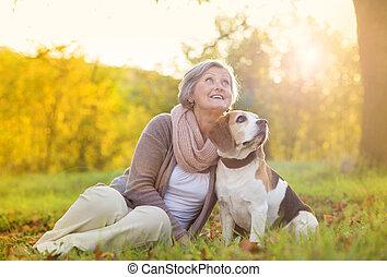 tätiger älterer, frau, hund, umarmungen