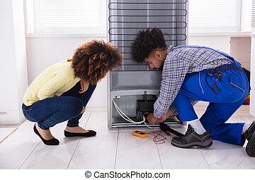 técnico, examinando, multímetro, refrigerador, digital