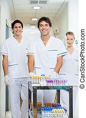 técnicos, con, médico, carrito, en, pasillo del hospital