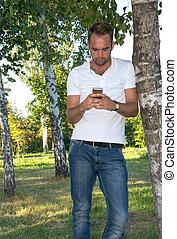 téléphone portable, parc, jeune homme