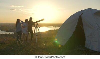 télescope, couple, jeune, appeler, regarder, leur, par, colline, coucher soleil, ami