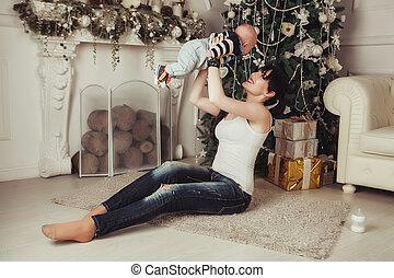 tête, faire idiot, mère, tient, arbre, jeune femme, au-dessus, enfant, bébé, portrait, fireplace., noël, heureux