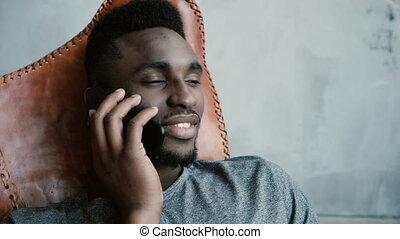 tête, sien, agreeing., séance, rire, jeune, conversation, nods, africaine, portrait, chaise, mâle, smartphone., homme