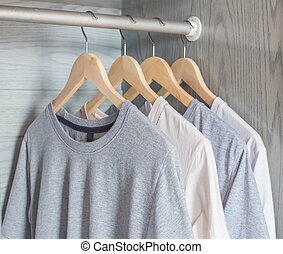 shirt - T-shirt hanging on wood hanger on rack in cloth...