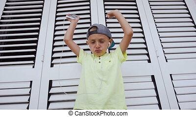 t-shirt, mignon, peu, smartphone, exécute, danse, il, improvisé, garçon, casquette, écoute, regarder, appareil photo, musique, fond, enfant, téléphone., blanc, apprécier, écouteurs, écoute