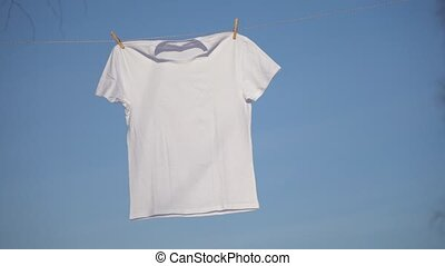T-shirts hanging on the clothesline against blue sky