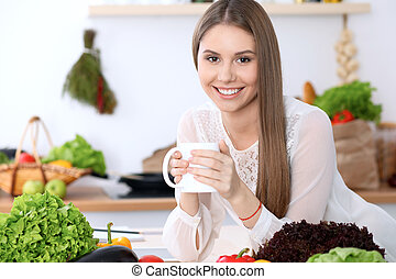tabela, segurando, legumes, madeira, copo, sentando, enquanto, olhar, branca, câmera, mulher, verde, feliz, cozinha, jovem