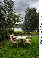 tabla, y, sillas, en, césped, por, lago, en, frío, día de otoño