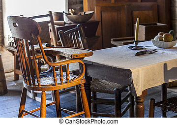 Table and baby chair in very old kitchen