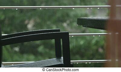 Table and chair on terrace in the rain