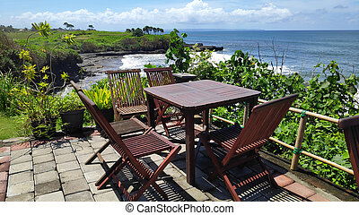 Table and chair with view of cliff and ocean near Tanah Lot, Bali