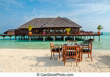 Table and chairs at restaurant at the background of water bungalows, Maldives island