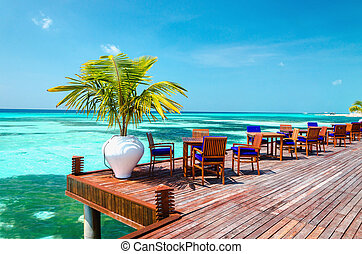 Table and chairs at water restaurant at the background of the blue sky, Maldives island