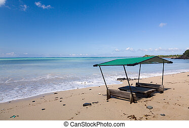 Table and chairs covered by sand on beach