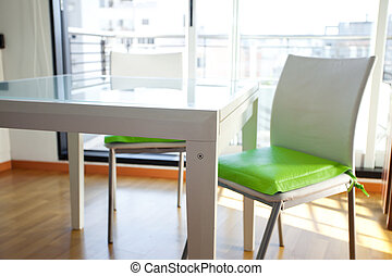 table and chairs in front of windows in the room