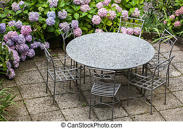 table and chairs in garden with color hydrangea